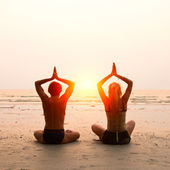 Young couple sitting on the beach of the sea in the lotus position at sunset — Stock Photo