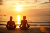 A young couple sitting on the beach of the sea in the lotus position at sunset. Yoga practice. — Stock Photo