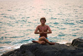 Man doing yoga exercise on the deserted wild stone sea beach — Stock Photo