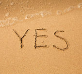 Yes - written in sand on beach texture - soft wave of the sea. — Stock Photo
