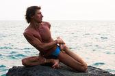 Giovane uomo facendo esercizio di yoga sulla spiaggia deserta selvaggio mare pietra — Foto Stock