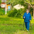 Active old woman nordic walking outdoors (85 years) — Stock Photo