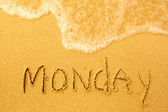 Monday - written in sand on beach texture - soft wave of the sea (days week series) — Stock Photo