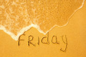 Friday - written in sand on beach texture - soft wave of the sea (days week series) — Stock Photo