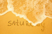 Saturday - written in sand on beach texture - soft wave of the sea (days week series) — Stock Photo