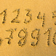Royalty-Free Stock Photo: Numbers one to ten written on a sandy beach.
