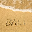 Stock Photo: Bali - written in sand on beach texture - soft wave of the sea.