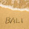 Bali - written in sand on beach texture - soft wave of the sea. — Stock Photo