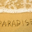 Paradise - written in sand on beach texture - soft wave of the sea - Foto Stock