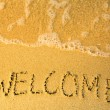 Welcome - written in sand on beach texture - soft wave of the sea — Stockfoto