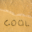 Cool - written in sand on beach texture - soft wave of the sea — Stok fotoğraf