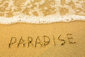 Paradise - written in sand on beach texture - soft wave of the sea — Stock Photo