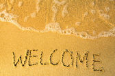 Welcome - written in sand on beach texture - soft wave of the sea — Stock Photo