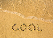Cool - written in sand on beach texture - soft wave of the sea — Stock Photo