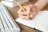 在一本笔记本,键盘,一摞书在背景中写入的手 — 图库照片