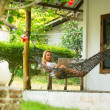 Beautiful girl lies in the hammock with laptop. — Stok fotoğraf