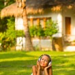 Beautiful emotional girl with headphones enjoying nature and music at sunny day. — Stock fotografie