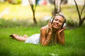 Lycka känslomässiga flicka med hörlurar som njuter av naturen och musik på solig dag. — Stockfoto