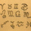 Stock Photo: Set of zodiac signs drawn on sand.