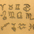 Set of zodiac signs drawn on sand. - Stockfoto