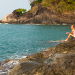 Girl is sitting on the rocks at the seaside. — ストック写真