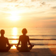 A young couple sitting on the beach of the sea in the lotus position — Stock Photo #23091006