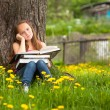 Tired teen-girl in the park with books — Stockfoto