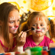 Young funny sisters playing with painting — Stock Photo