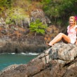 Girl is sitting on the rocks at the seaside. — Stockfoto