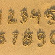 Numbers written on a sand - Stock Photo