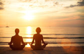 A young couple sitting on the beach of the sea in the lotus position — Stock Photo