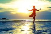 Pratik yoga sahilde kadın — Stok fotoğraf