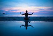 女人练瑜伽在海滩上 — 图库照片