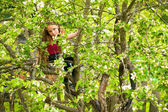 Teen-girl posing sitting on a tree in the garden. — Stock Photo