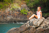 Girl is sitting on the rocks at the seaside. — Stock Photo