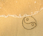 Yin yang symbol - written on sand — Stock Photo