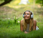 Girl with headphones enjoying nature and music — Стоковое фото