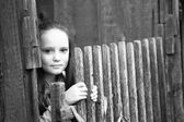 Teen-girl standing near vintage rural fence, black-and-white photo. — Stock Photo