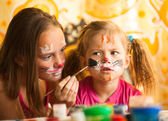Sisters playing with painting. — Stock Photo