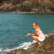 Stock Photo: Blonde girl is sitting on the rocks at seaside.