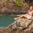 Blonde girl is sitting on the rocks at the seaside. — Stock Photo