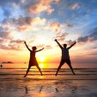 Young couple in a jump on the sea beach at sunset (concept of long-awaited vacation) - Stock Photo