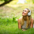Lovely girl with headphones enjoying nature and music at sunny day. — Foto Stock #24685193