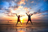 Young couple in a jump on the sea beach at sunset (concept of long-awaited vacation) — Stok fotoğraf