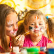 Stock Photo: Two little funny sisters playing with painting