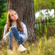Teen-girl writing in a notebook while sitting in park. — Stock Photo #24704703