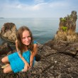 Teengirl in a blue dress in the rocks of the coast in Thailand. — Foto de Stock