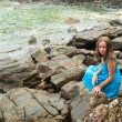 Teen-girl in a blue dress in the rocks of the coast. — Stock Photo #24704717