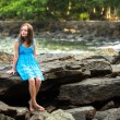 Teen-girl in a blue dress in the rocks of the coast. — Стоковая фотография