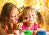 Two little funny sisters playing with painting — Стоковое фото